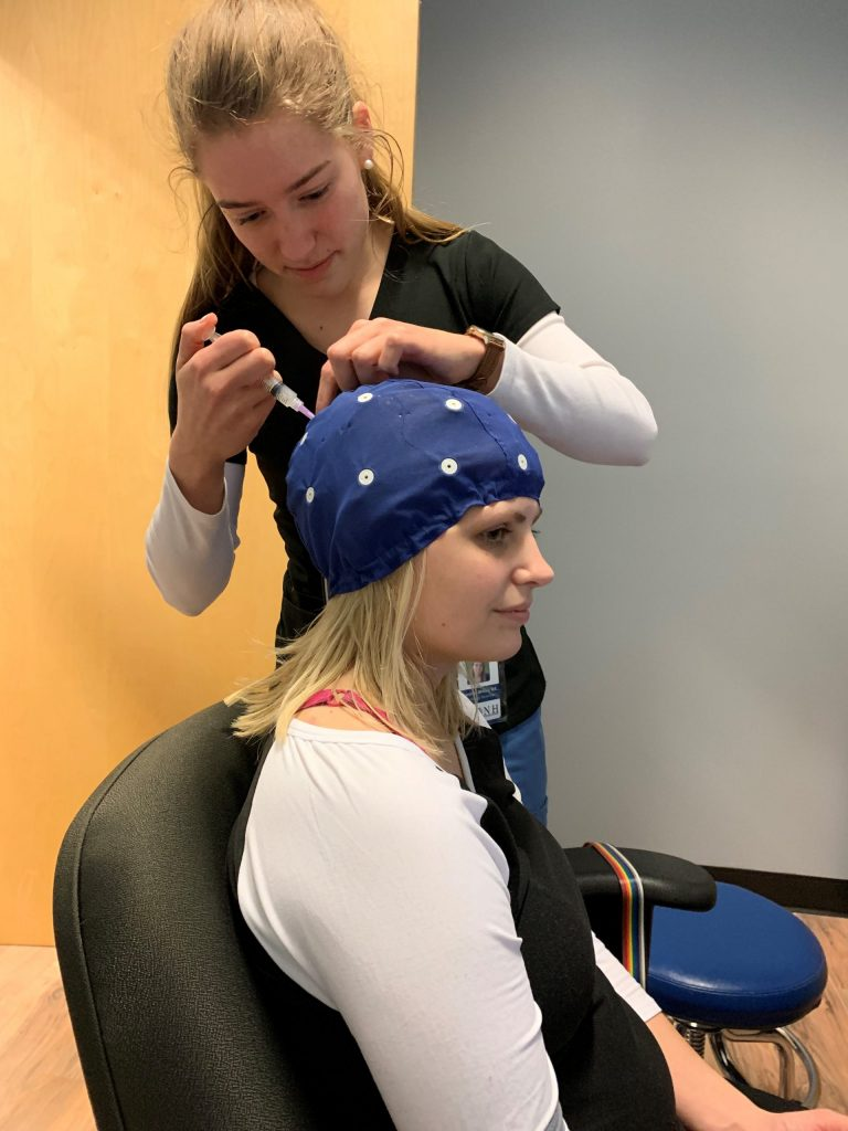 EEG cap being applied to adult test subject