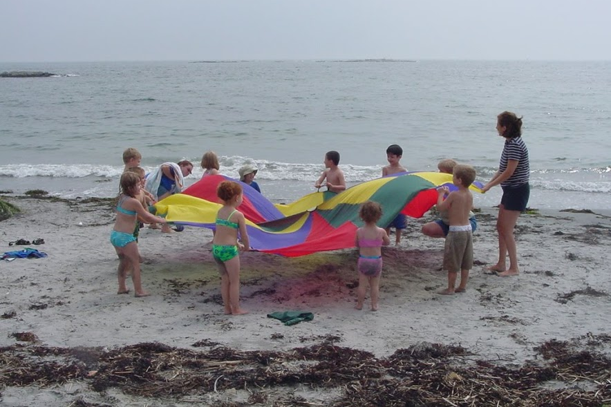 Supervised group of children playing with a parachute on the beach