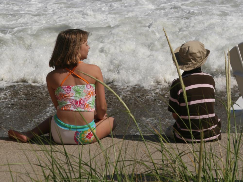 Kids sitting in the sand watching ocean waves